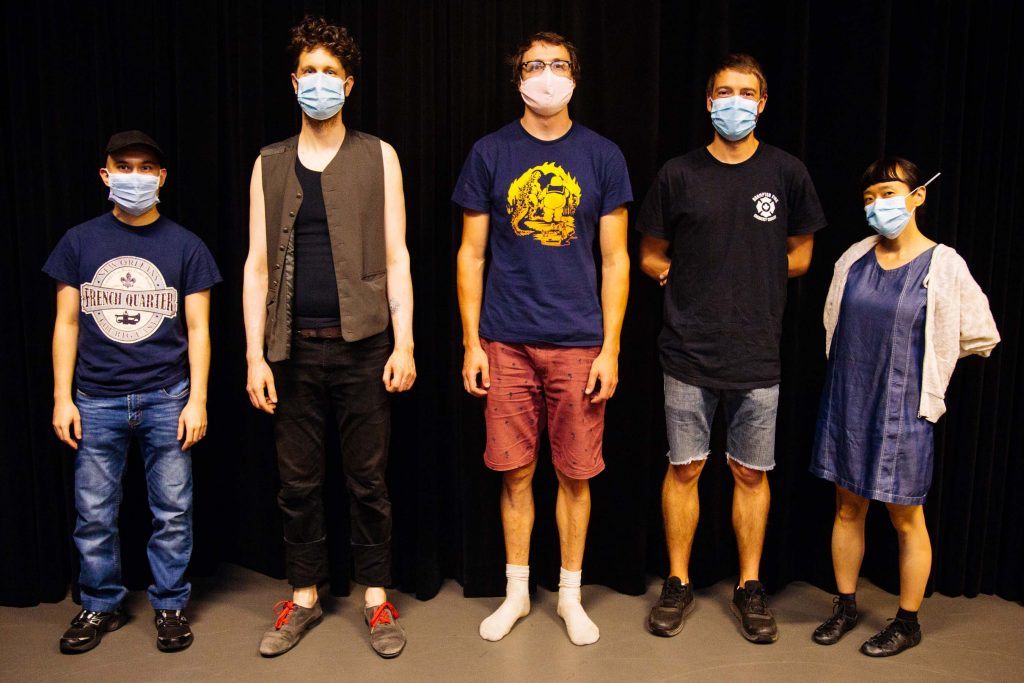 5 people wearing masks are lined up with spaces in between them. They are looking right at you.