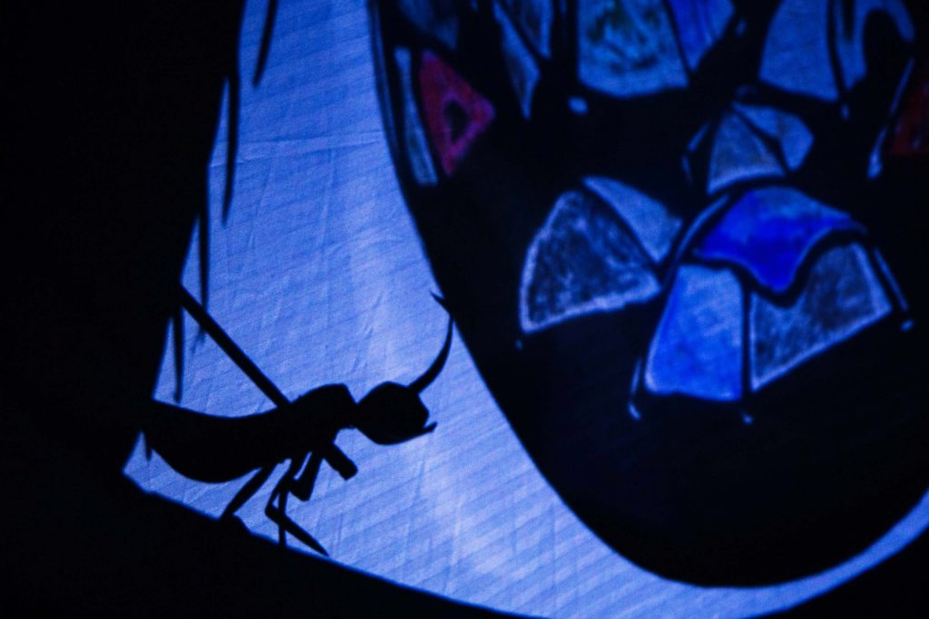 Earwig puppet shadow perching on the edge of an eye shadow. Inside the eye, there are tent shadows in blue light.