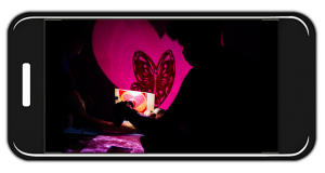 On a mobile phone screen, there's a red butterfly in the shape of a heart projected on the Home Squat Home tent shadow puppet screen.