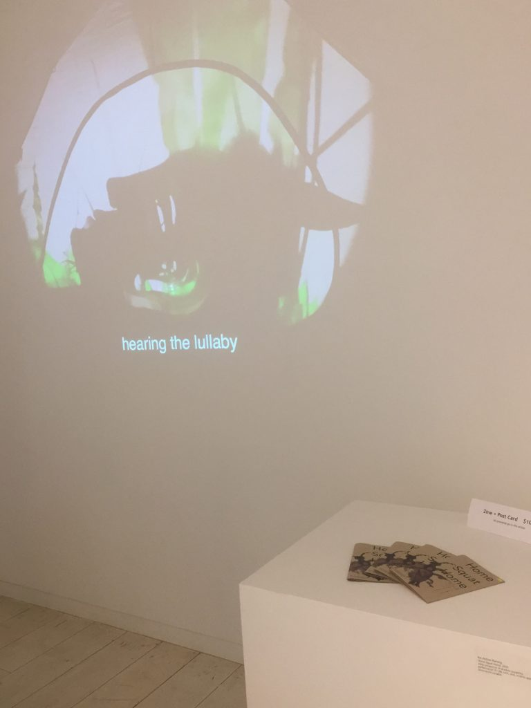 """A projection on the wall shows the profile of a shadow puppet head, resting on the ground surrounded by green grass. An earwig crawls on the head. The eye is visible as a double slit, letting light through, and through the ear we see green grass. Captions at the bottom center of the projection read """"hearing the lullaby."""" Beside the projection a plinth holds several Home Squat Home zines."""