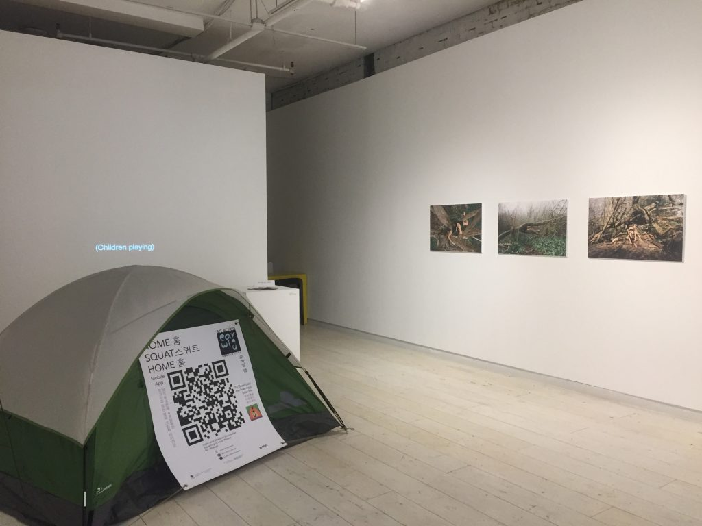 """A green tent with a light grey cover is set on a wood planked floor in a white walled gallery space. Behind the tent a projection on the wall is dark. Captions at the bottom center of the projection read """"(Children playing)."""" Beside the projection a plinth holds several Home Squat Home zines. On another wall to the right the projection and plinth, three photographs by photographer Neena Robertson hang. Each photograph depicts a person's body entangled with the branches of trees in a twisted leafless grove. Patches of soil alternate with patches of vibrant green bush. The photography series, Hide and Seek, was created at a former camping site of unhoused residents on the unceded traditional territory of the lək̓ʷəŋən peoples on the Esquimalt and Songhees Nations (known as Victoria BC). A banner on the tent reads in both English and Korean """"Home Squat Home mobile app"""" at the top left and """"art action earwig"""" at the top right. A large QR code occupies the center of the banner. The words """"To download the free app scan me"""" are on the right side of the QR code along with the app Icon, an abstract black earwig in front of an orange tent, with a purple ground and green sky. The words """"Light and shadow story-teller squatting on your phone for 49 days"""" are found at the bottom center above funder logos."""
