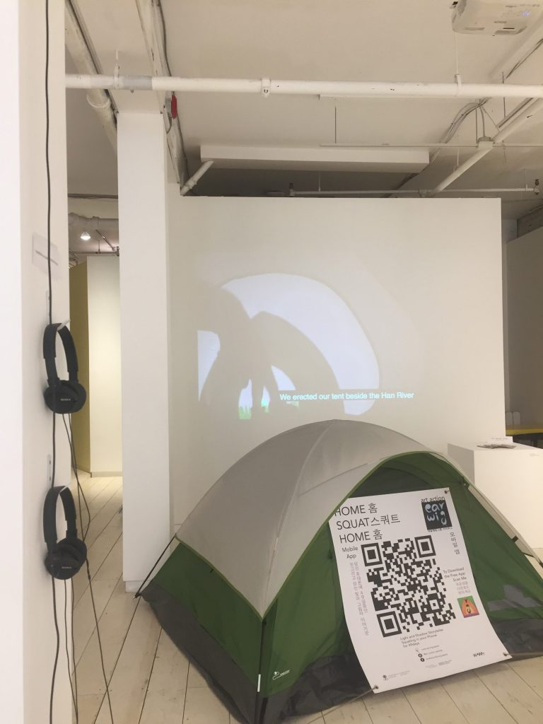 """A green tent with a light grey cover is set on a wood planked floor in a white walled gallery space. Behind the tent a projection on the wall shows a shadow puppet tent, two fingers in shoes and green grass. Captions at the bottom center of the projection read """"We erected our tent beside the Han river."""" Beside the projection a plinth holds several Home Squat Home zines. In the foreground two black headphone sets hand on the wall. A banner on the tent reads in both English and Korean """"Home Squat Home mobile app"""" at the top left and """"art action earwig"""" at the top right. A large QR code occupies the center of the banner. The words """"To download the free app scan me"""" are on the right side of the QR code along with the app Icon, an abstract black earwig in front of an orange tent, with a purple ground and green sky. The words """"Light and shadow story-teller squatting on your phone for 49 days"""" are found at the bottom center above funder logos."""
