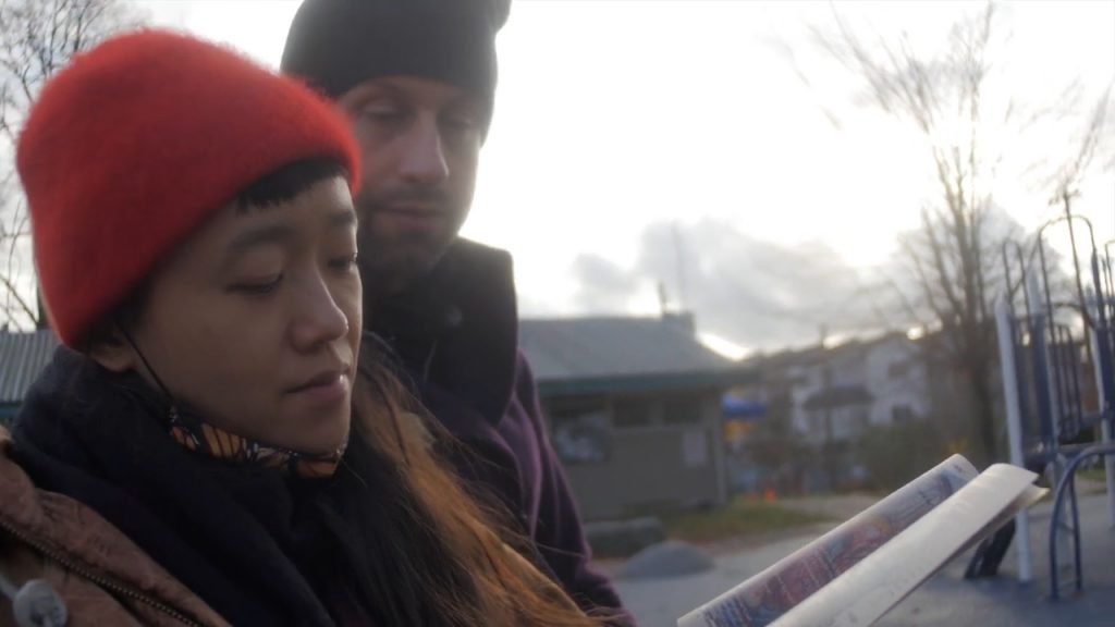 Minah and Wryly sit in Pandora Park looking reading from a copy of their Home Squat Home zine. Minah is in the foreground with a bright red toque, eyes cast down on the zine. Wryly is behind Minah wearing a black toque and purple winter coat, eyes cast down on the zine. A playground and field house are in the distance behind them, along with some trees and houses. The sky is overcast in a blaring grayish white that swallows the trees.